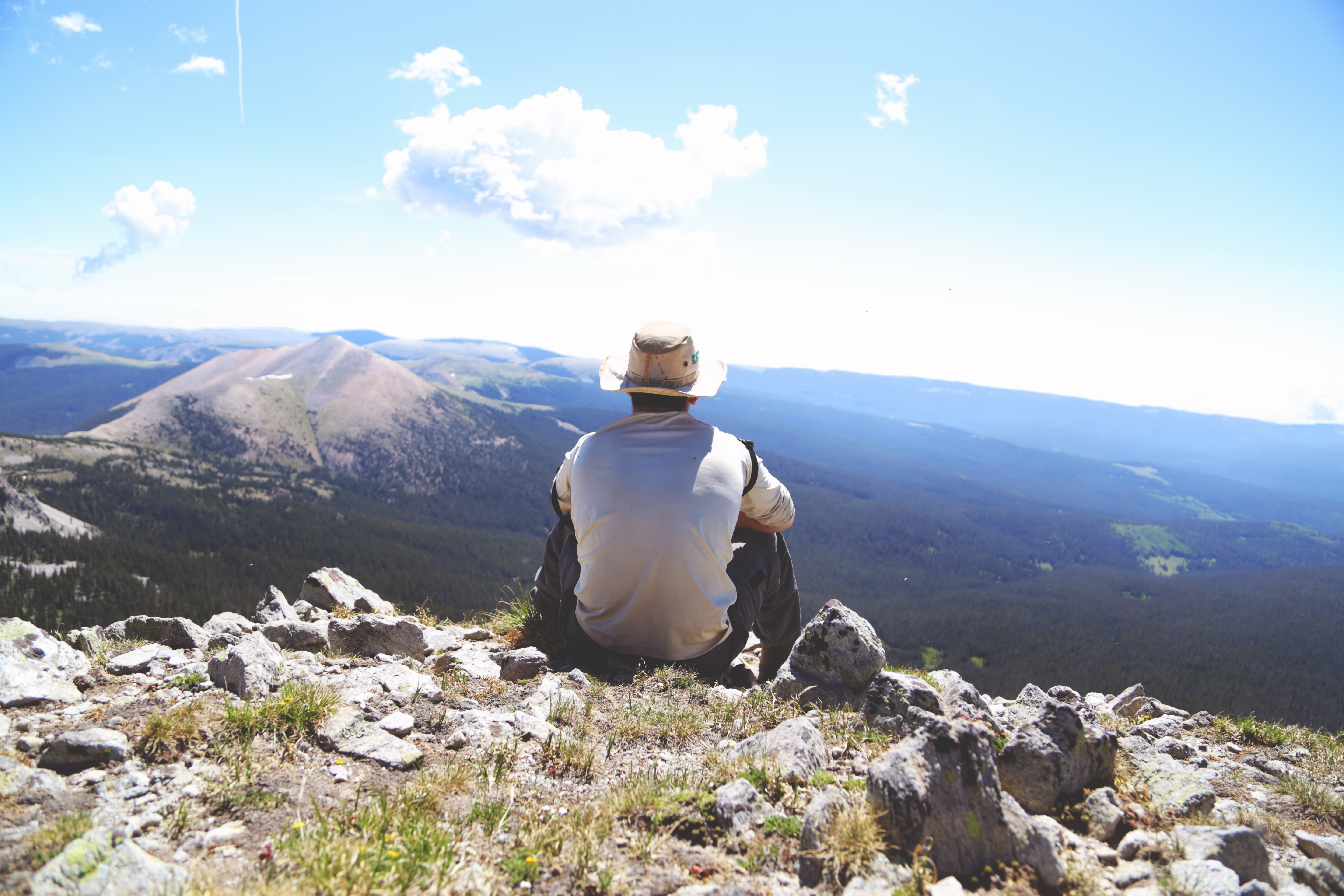 Man sitting on top of a mountain